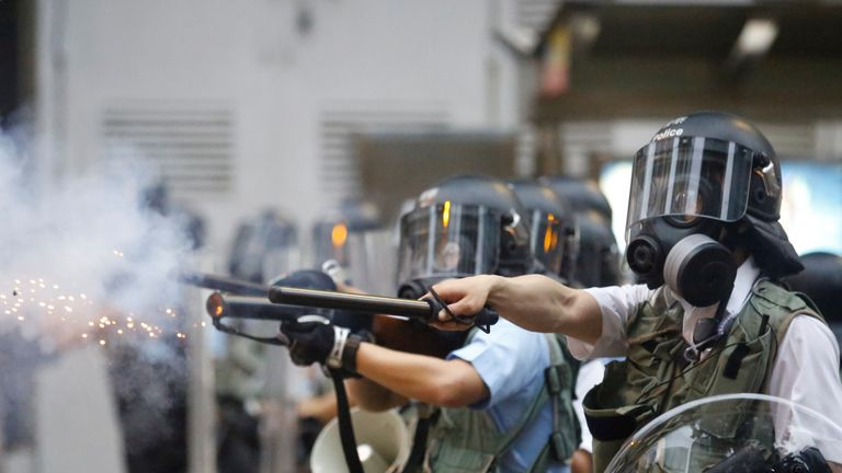 Police officers fire tear gas at demonstrators in Hong Kong