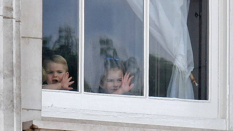 Prince Louis (L) and Princess Charlotte wave from a window in Buckingham Palace before the RAF fly-past