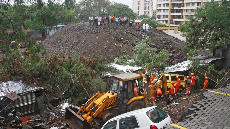 Rescue workers look for survivors among the debris of a collapsed wall in Pune