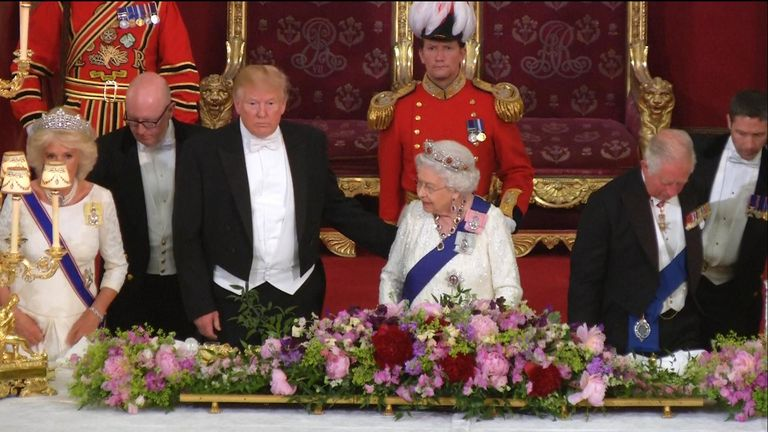 President Trump appeared to breach accepted royal protocol by touching the Queen on the back as she rose for his toast.