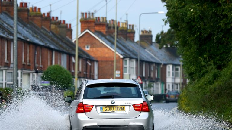 "A car passes through a flooded road in Rye, East Sussex as thunderstorms powered up by a plume of warm continental air have begun to unload ""hefty downpours"" and flashes of lightning over south-east England"