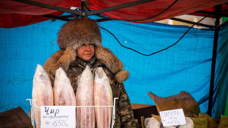 A vendor sells frozen fish in Yakutsk, Siberia, with the temperature at -35C