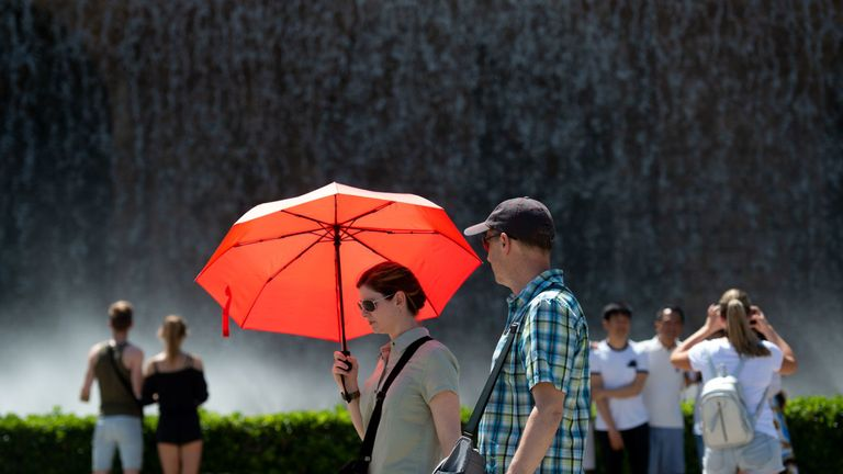 Tourists cool off at the Mountjuic fountain in Barcelona