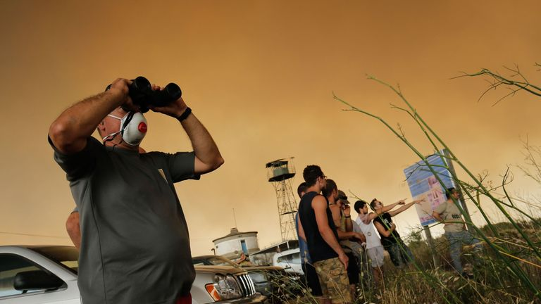 Residents gather to observe a forest fire raging near Maials in the northeastern region of Catalonia on June 27, 2019. - A Spanish forest fire raged out of control amid a European heatwave, devouring land as hundreds of firefighters battled through the night, local authorities said. (Photo by Pau Barrena / AFP) (Photo credit should read PAU BARRENA/AFP/Getty Images)
