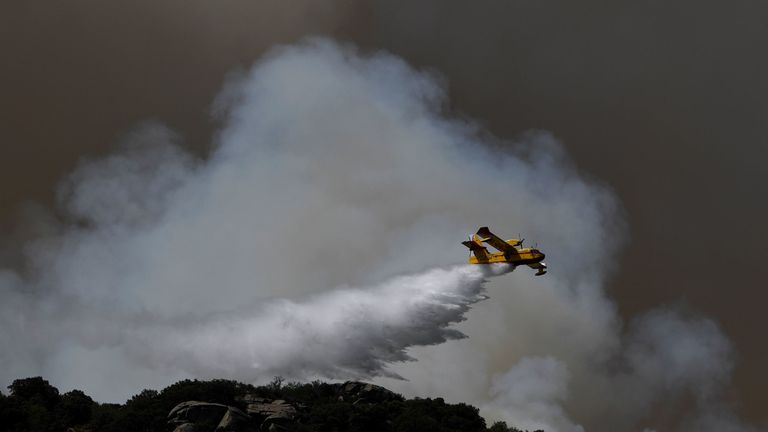 Water is dropped on a wildfire in central Spain