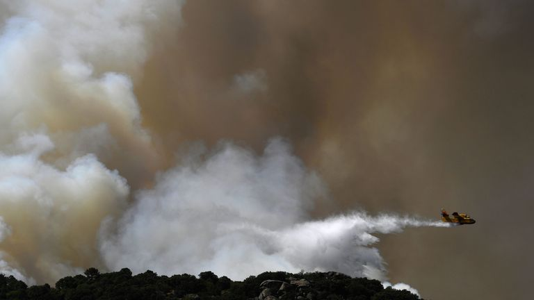 A plane drops water over a wildfire in Catalonia, Spain