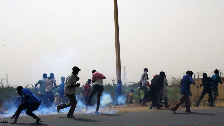 Protesters dodge tear gas canisters fired during the protest