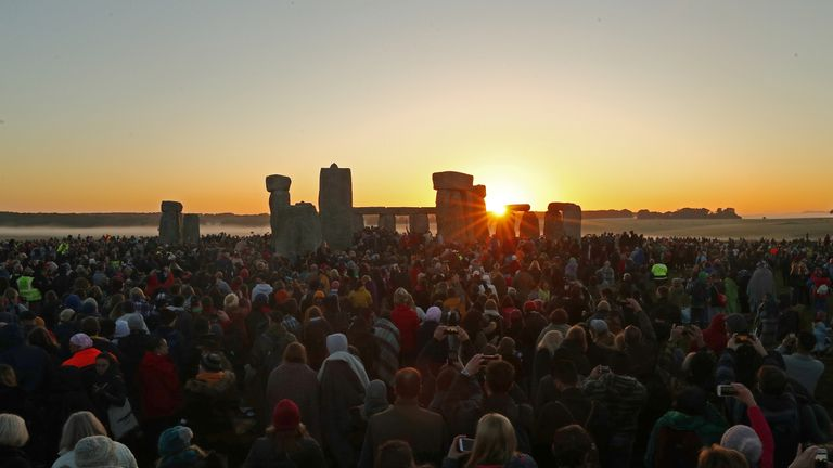 The sun rises as revellers welcome in the Summer Solstice at the Stonehenge stone circle