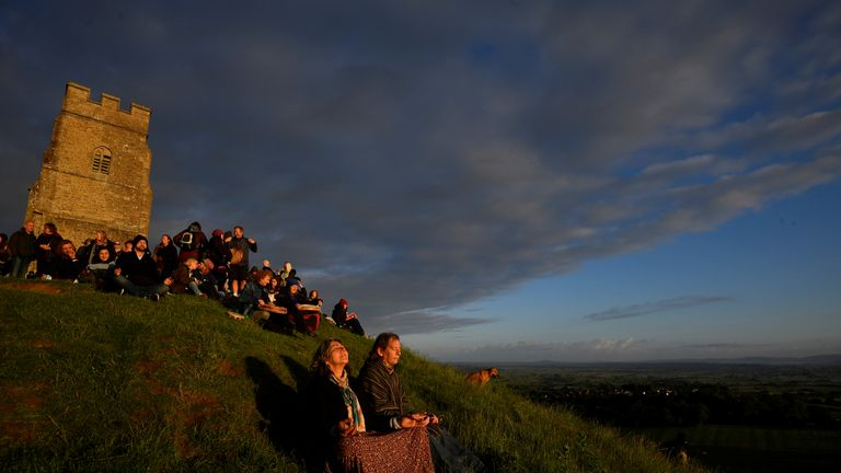 Revellers celebrate the Summer Solstice as the sun rises at Glastonbury Tor