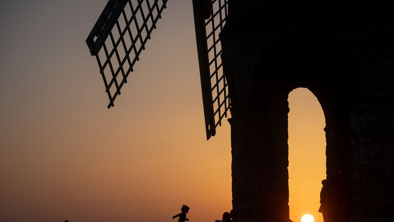 The sun sets by Chesterton Windmill in Warwickshire. The UK is enjoying a warmer spell of weather whilst temperature records are broken across many parts of Europe