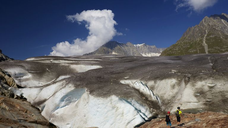 Hikers stand on the side of the Aletsch Glacier in Fiesch, Switzerland, in 2015