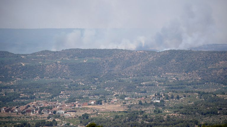 A smoke column is seen during a forest fire near La Granadella, west of Tarragona, Spain