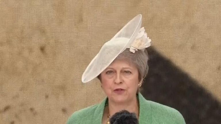 Theresa May reads on stage at the D-Day commemorations in Portsmouth