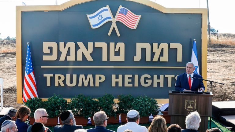 "Israeli Prime Minister Benjamin Netanyahu gives a speech before the newly-unveiled sign for the new settlement of ""Ramat Trump"", or ""Trump Heights"" in English, named after the incumbent US President during an official ceremony in the Israeli-annexed Golan Heights on June 16, 2019"