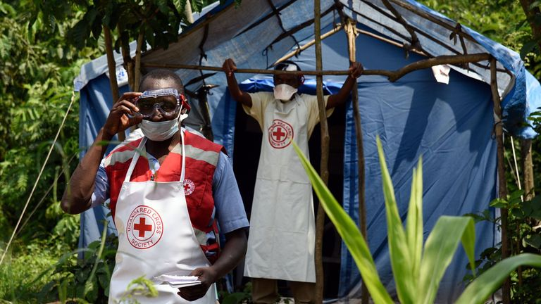 Health workers stand at a non-gazetted crossing point in the Mirami village, near the Mpondwe border check point between Uganda and the Democratic Republic of Congo