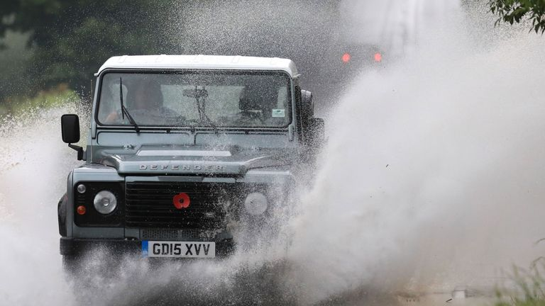 A Land Rover crashes through standing water on a road near Tenterden in Kent, following heavy rain