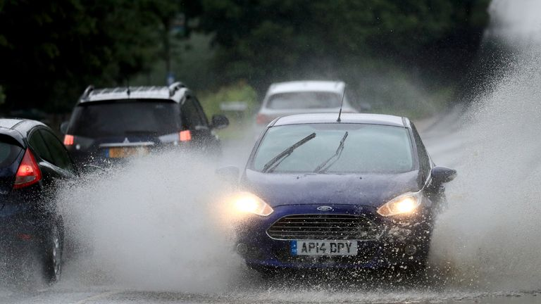 A car crashes through standing water on a road in Kent following heavy rain
