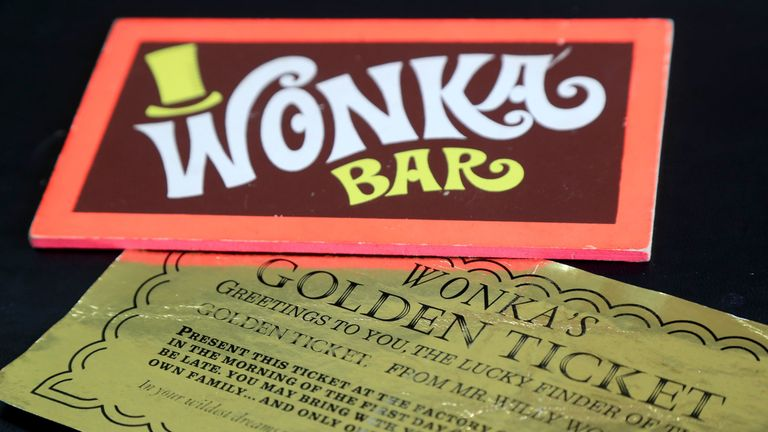 Two iconic film props - a Wonka Bar and a golden ticket