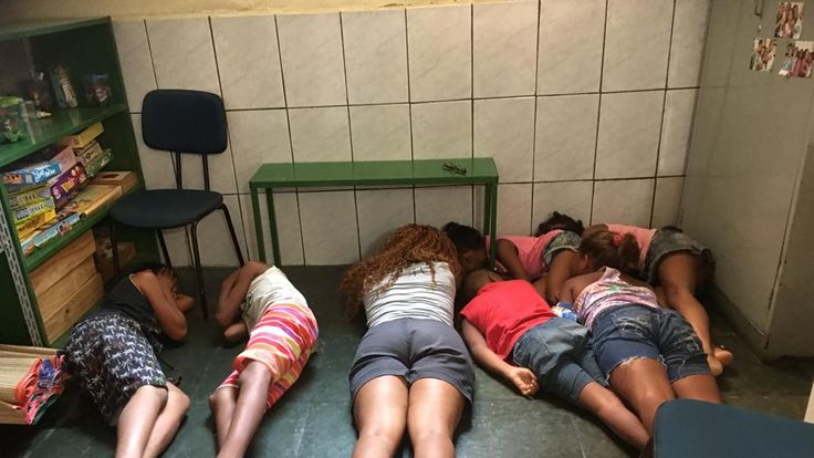 Children at Uere school in Rio de Janeiro throw themselves to the floor to dodge bullets