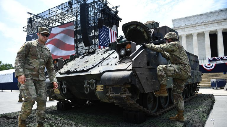 "Members of the US military are seen next to a Bradley Fighting Vehicle as preparations are made for the ""Salute to America"" Fourth of July event with US President Donald Trump at the Lincoln Memorial on the National Mall in Washington, DC, July 3, 2019, which will feature flyovers by the Blue Angels, an airplane used as Air Force One, as well as military demonstrations and a speech by Trump. (Photo by Brendan Smialowski / AFP)        (Photo credit should read BRENDAN SMIALOWSKI/AFP/Getty Images)"