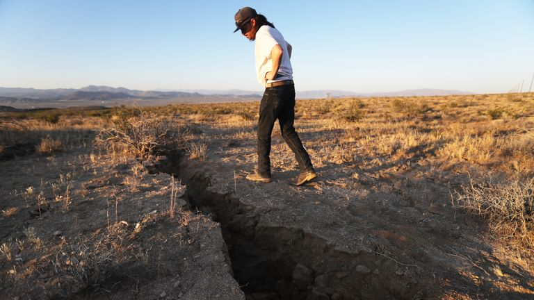 RIDGECREST, CALIFORNIA - JULY 04: A local resident inspects a fissure in the earth after a 6.4 magnitude earthquake struck the area on July 4, 2019 near Ridgecrest, California. The earthquake was the largest to strike Southern California in 20 years with the epicenter located in a remote area of the Mojave Desert. The temblor was felt by residents across much of Southern California. (Photo by Mario Tama/Getty Images)