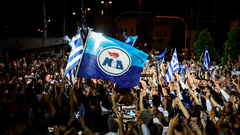 Supporters of the Greece's newly elected Prime Minister and leader of conservative New Democracy party Kyriakos Mitsotakis, celebrate outside the party's headquarters after the official results of the elections in Athens on July 7, 2019. - Greek Prime Minister Alexis Tsipras conceded defeat in a general election to Kyriakos Mitsotakis, head of the conservative New Democracy party, his office said. Leftist Tsipras called Mitsotakis to congratulate him, a source in the prime minister's office told AFP, with New Democracy on track to score a landslide victory according to early results. (Photo by ANGELOS TZORTZINIS / AFP)        (Photo credit should read ANGELOS TZORTZINIS/AFP/Getty Images)