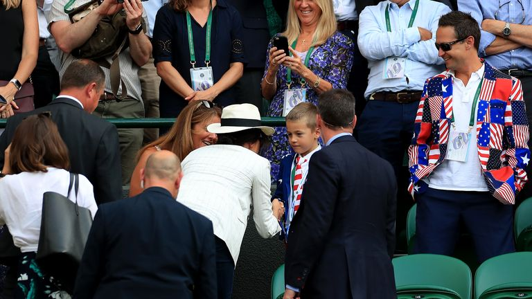 Duchess of Sussex shakes hands with a young spectator dressed in Star Spangled Banner attire on day four of the Wimbledon Championships at the All England Lawn Tennis and Croquet Club, Wimbledon.