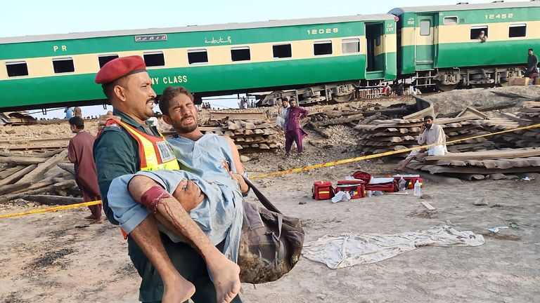 A Pakistani rescuer carries an injured passenger at the site of train accident in Rahim Yar Khan district in Punjab province on July 11, 2019. - t least nine people were killed and more than 60 injured when two trains collided in central Pakistan early July 11, officials said. The incident took place in Rahim yar Khan district in Punjab province when a passenger train coming from the eastern city of Lahore rammed into a goods train that had stopped at a crossing, a senior government official said. (Photo by STR / AFP)        (Photo credit should read STR/AFP/Getty Images)
