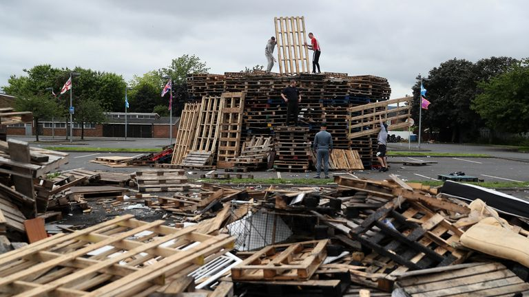 People add to the 11th night bonfire at Avoniel Leisure Centre as councillors in Belfast have agreed not to remove the loyalist bonfire.