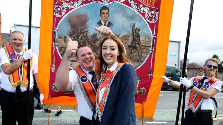 An Orange woman poses with Orange men during the annual Twelfth of July parade in Belfast, on July 12, 2019. - July 12 is the main marching day in the Protestant Orange Order calendar. The parades mark the commemoration of the victory by King William III - the Dutch-born Protestant better known as William of Orange or King Billy - over Catholic King James II at the Battle of the Boyne in 1690. (Photo by Paul Faith / AFP)        (Photo credit should read PAUL FAITH/AFP/Getty Images)