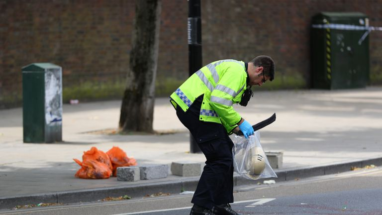 Police at the scene in Battersea, south-west London, where woman has died after being struck by a lorry while riding a scooter.