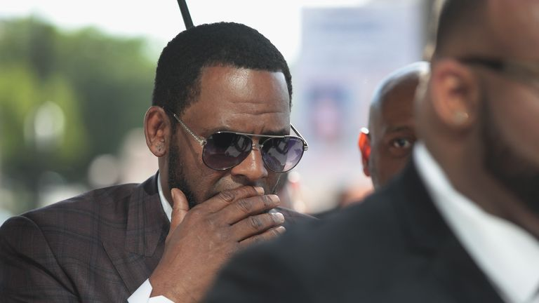 CHICAGO, ILLINOIS - JUNE 26: R&B singer R. Kelly covers his mouth as he speaks to members of his entourage as he arrives at the Leighton Criminal Courts Building for a hearing on June 26, 2019 in Chicago, Illinois.  Kelly is facing several counts of aggravated sexual abuse.  (Photo by Scott Olson/Getty Images)