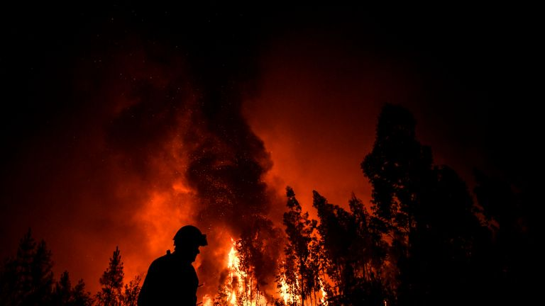 A firefighter passes while a wildfire burns the forest at Amendoa in Macao, central Portugal on July 21, 2019. - More than a thousand firefighters battled to control wildfires in central Portugal that have forced village evacuations, in a region where dozens were killed in huge blazes in 2017. The firefighters were deployed to tackle three fires in the mountainous and heavily forested Castelo Branco region, 200 kilometres north of Lisbon, according to the website of the Civil Protection. (Photo by PATRICIA DE MELO MOREIRA / AFP)        (Photo credit should read PATRICIA DE MELO MOREIRA/AFP/Getty Images)