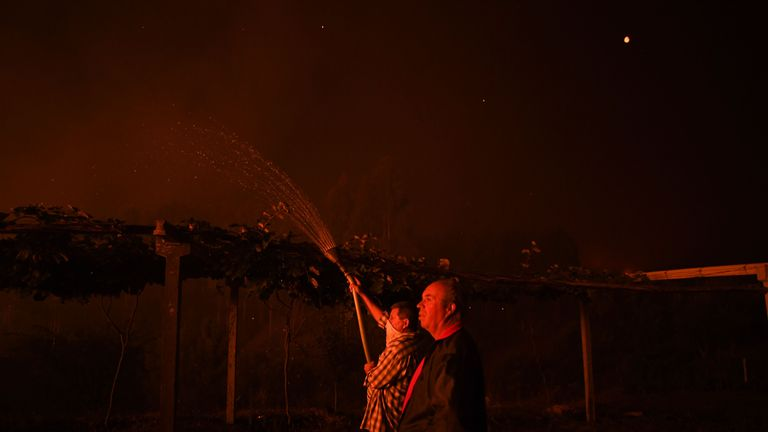 A villager holds a hose as a wildfire comes close to his house at Amendoa in Macao, central Portugal on July 21, 2019. - More than a thousand firefighters battled to control wildfires in central Portugal that have forced village evacuations, in a region where dozens were killed in huge blazes in 2017. The firefighters were deployed to tackle three fires in the mountainous and heavily forested Castelo Branco region, 200 kilometres north of Lisbon, according to the website of the Civil Protection. (Photo by PATRICIA DE MELO MOREIRA / AFP)        (Photo credit should read PATRICIA DE MELO MOREIRA/AFP/Getty Images)