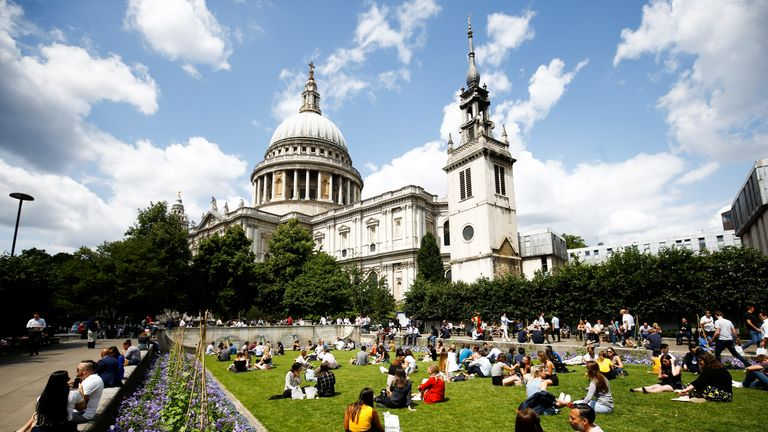 People relax in the warm weather near St Paul's Cathedral in central London, Britain July 12, 2019. REUTERS/Henry Nicholls