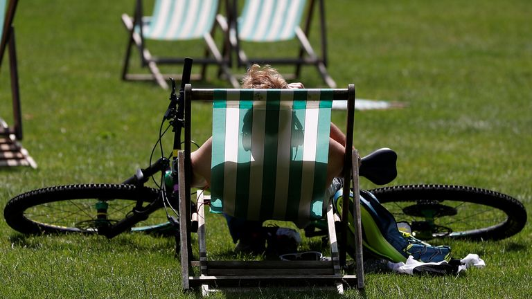 A cyclist rests in the sun in St James' Park in London, Britain, June 29, 2019. REUTERS/Peter Nicholls