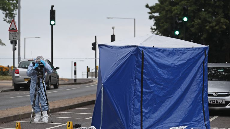 """A forensics officer on Moor Lane in Chessington following a hit-and-run incident where a man died after being """"dragged under a car""""."""