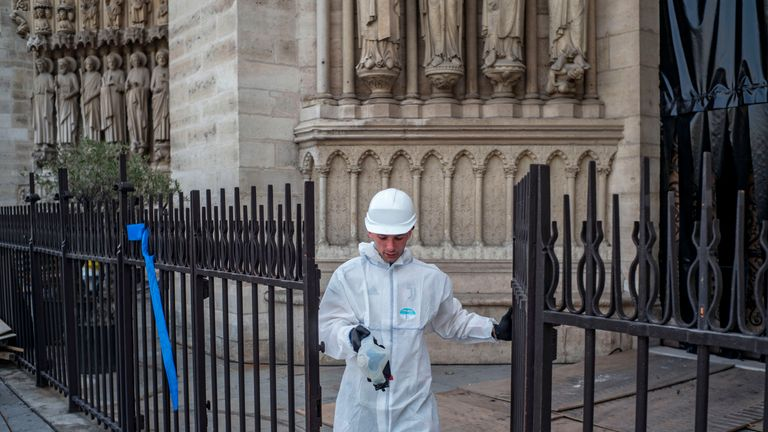 A construction worker walks through a gate at the Notre-Dame de Paris Cathedral during preliminary work on July 24, 2019 in Paris, three months after it was badly damaged by a huge fire last April 15. (Photo by Rafael Yaghobzadeh / POOL / AFP)        (Photo credit should read RAFAEL YAGHOBZADEH/AFP/Getty Images)