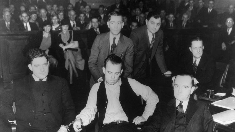 5th February 1934:  American criminal John Dillinger sits handcuffed to Deputy Chief Carroll Holby, beside his attorney Joseph Ryan while on trial in Crown Point, Indiana.  (Photo by American Stock/Getty Images)