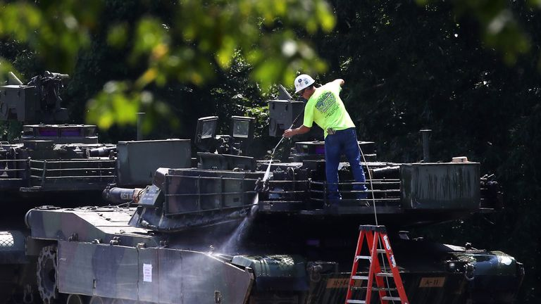A worker washes one of two M1A1 Abrams tanks that are loaded on rail cars at a rail yard on July 2, 2019 in Washington, DC. President Trump asked the Pentagon for military hardware, including tanks, to be displayed during Thursdays July 4th Salute to America celebration at the Lincoln Memorial