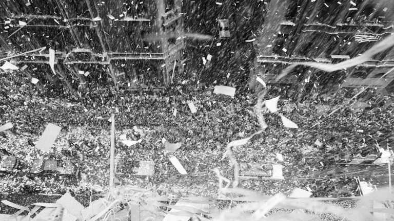 An avalanche of confetti rains down upon a cheering crowd and the three astronauts of the Apollo 11 mission in New York City