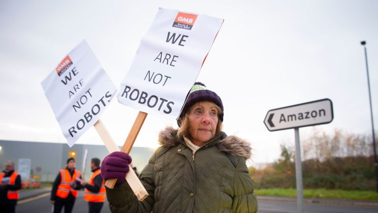 SWANSEA, WALES - NOVEMBER 23: A representative from GMB, the union for Amazon workers, stages a protest over what it claims are 'inhuman conditions' at the Amazon Swansea fulfillment centre at Ffordd Amazon on November 23, 2018 in Swansea, Wales. Protests are being held at five Amazon sites across the UK on Black Friday. Amazon recently increased wages for 40,000 permanent and temporary staff to £10.50 an hour in London and £9.50 across the rest of the country. (Photo by Matthew Horwood/Getty Im