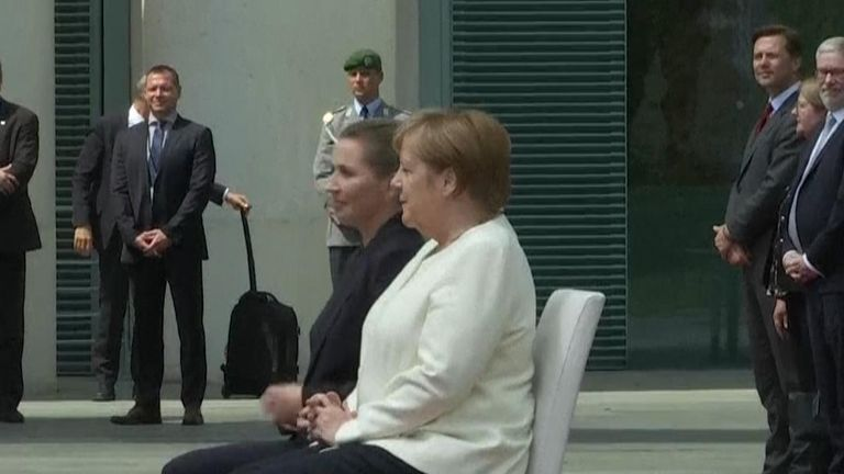 Angela Merkel takes a seat for the national anthem