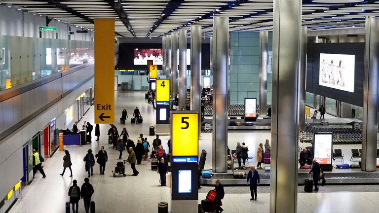 Passengers collect their luggage from the baggage reclaim area at Heathrow Airport