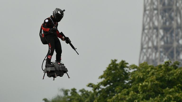 "Zapata CEO Franky Zapata flies a jet-powered hoverboard or ""Flyboard"" prior to the Bastille Day military parade down the Champs-Elysees avenue in Paris on July 14, 2019. (Photo by Lionel BONAVENTURE / AFP) (Photo credit should read LIONEL BONAVENTURE/AFP/Getty Images)"