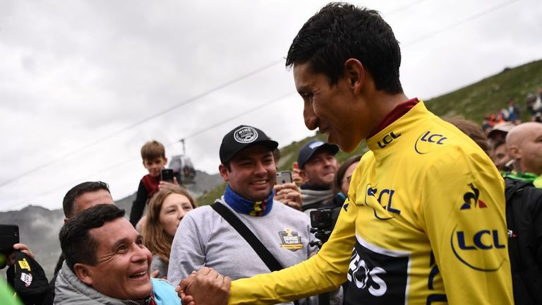 Colombia's Egan Bernal (R), wearing the overall leader's yellow jersey meets a fan after the podium ceremony of the twentieth stage