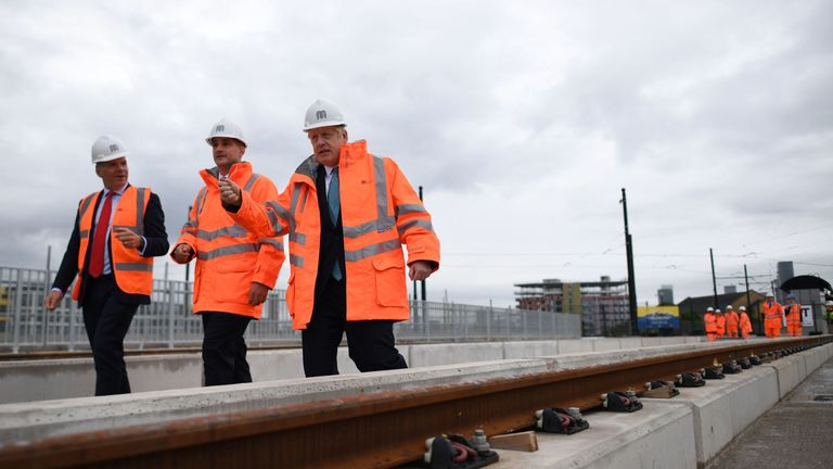 Britain's Prime Minister Boris Johnson (R) walks with CEO of Transport for the North, Barry White (L) and Britain's Northern Powerhouse Minister, Jake Berry as he leaves the site of an under-construction tramline in Stretford, greater Manchester, northwest England on July 27, 2019, prior to giving a speech focusing on domestic priorities. (Photo by Ben STANSALL / POOL / AFP) / The erroneous mention[s] appearing in the metadata of this photo by Ben STANSALL has been modified in AFP systems in the