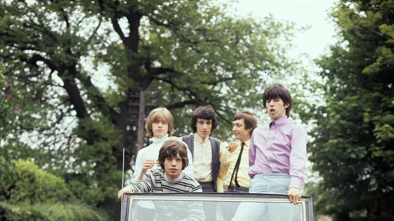 The Rolling Stones pose in a vintage car in 1964