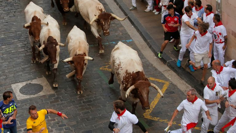 Bulls chase runners through the streets of Pamplona