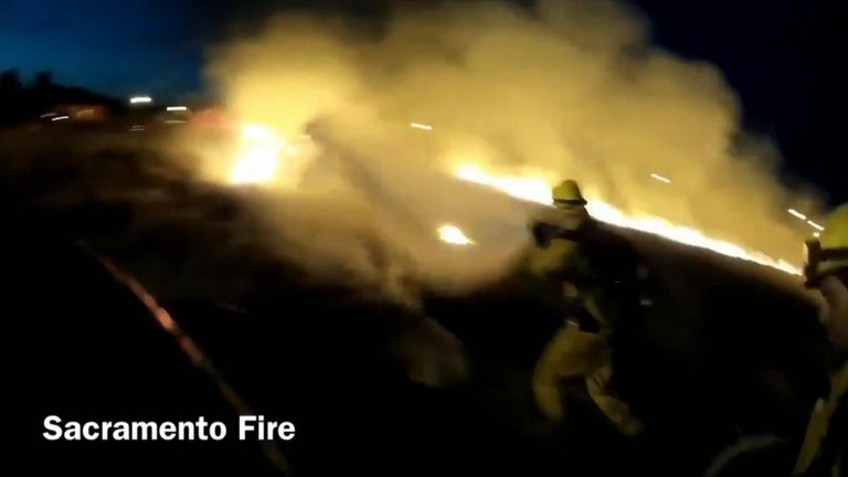 A grass fire believed to have been ignited by fireworks burned through several acres of land in Sacramento, California.